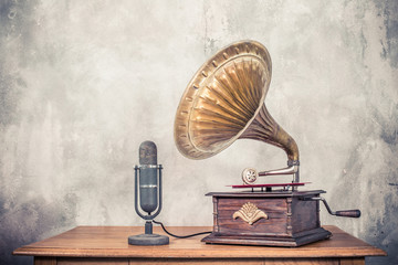 Vintage antique gramophone phonograph turntable with brass horn and big aged studio microphone on wooden table front concrete wall background. Retro old style filtered photo
