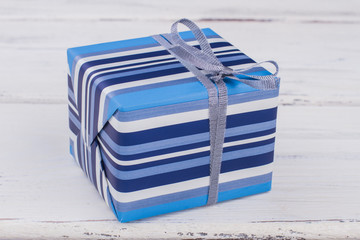 Blue and white stripes gift box. Present box wrapped in striped paper. Holiday celebration concept.