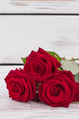 Three red roses and copy space. Beautiful red flowers on wooden background, vertical image. Valentines Day greeting card.