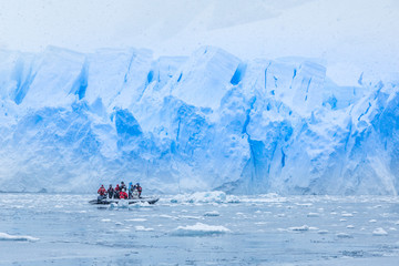 Snowfall over boat with tourists in the bay full of icebergs with huge glacier wall in the background, near Almirante Brown, Antarctic peninsula