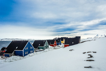 Colorful inuit houses along the street covered in snow, at the fjord in a suburb of arctic capital Nuuk, Greenland