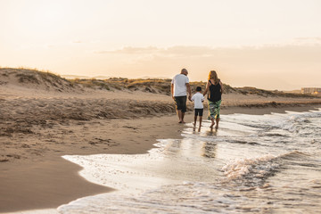 Family walking on beach sand in the sun. Nice family reunited if summer vacation