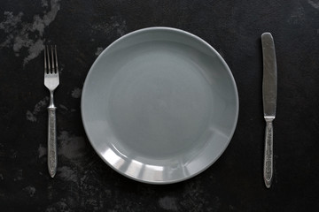 Empty gray plate and vintage fork and knife, black stone background. Top view