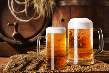Tuinposter Bier / Cider Two mugof beer .With wheat and barley and barrels spikes on bakcground.Still life