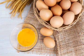 Eggs in a wooden basket and yolk in a bowl on a white wooden table.