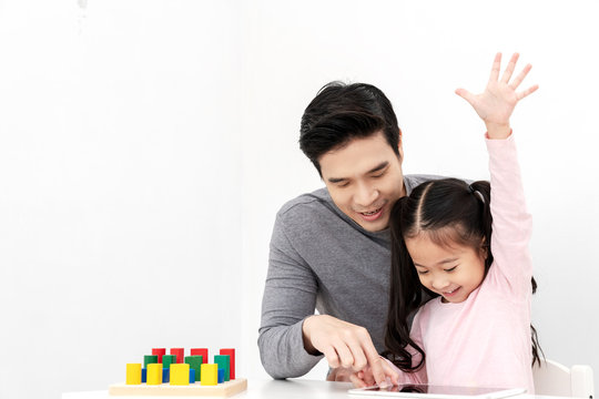 Young single dad play smart gadget and have fun with daughter sitting on kid desk table with colorful block toy beside copy space on isolated white background. Home school or preschool kids concept.