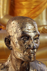 Statue of a monk with head and face covered in gold leaf at a Buddhist temple in south east Asia.