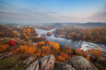 amazing aerial view of mountain rocks, blue foggy river and colorful forest on sunrise. autumn landscape