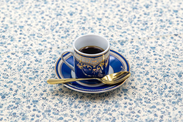 isolated classic blue with gold motifs black coffee cup with golden spoon on flowers pattern tablecloth
