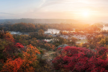 amazing aerial view of mountain rocks,  foggy river and colorful forest on sunrise. autumn landscape