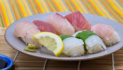 sushi plate with lemon slice, wasabi and soy sauce on bamboo set and colorful tablecloth close up