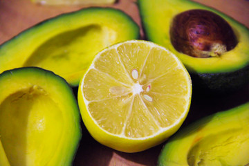 tasty ripe green avocado with brown bone and yellow lemon on a wooden board