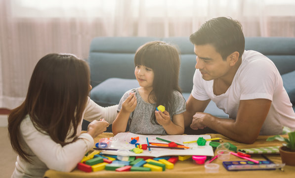 Portrait of happy family daughter girl is learning to use colorful play dough together with parent