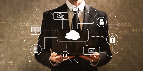 Cloud computing with businessman holding a tablet computer on a dark vintage background