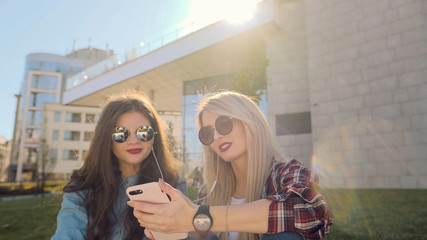 Two attractive hipster girls using smart phone.