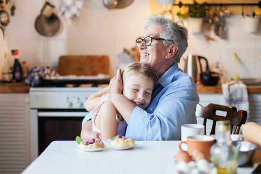 Happy grandmother is hugging granddaughter in cozy home kitchen. Family is cooking together. Senior woman and cute little child girl are smiling. Kid is enjoying kindness, warm hands, care, support.