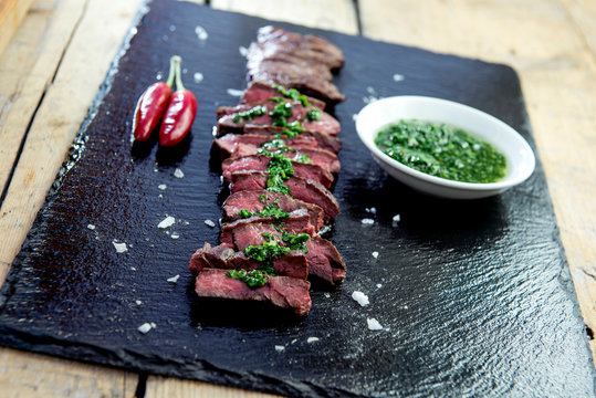 Black stone plate with skirt steak pepper and chimichurri sauce