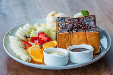 The fruits toast with icecream on black dish