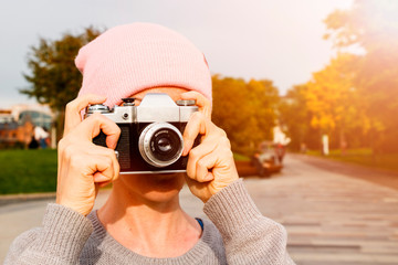 girl takes pictures on the old vintage camera in the park