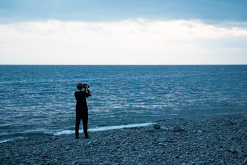 A young man with a camera on the background of the ocean. Selective focus.