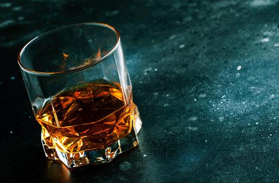 Bourbon in glass, american corn whiskey, dark bar counter, selective focus