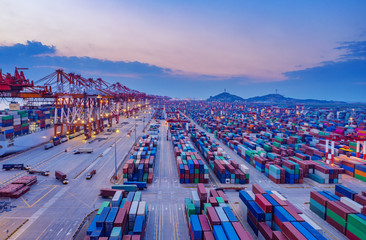 Fototapeta Container ship in export and import business and logistics. Shipping cargo to harbor by crane. Water transport International. Aerial view