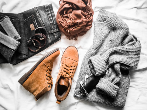Set of women's outfits autumn, winter clothes  - jeans, gray pullover oversize, suede brown boots. Fashionable casual clothes for walks, flat lay. On a light background