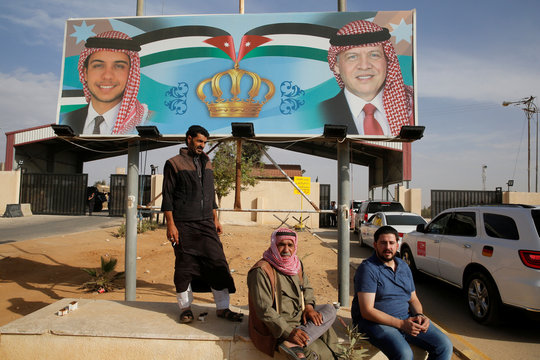 People sit next of a billboard with a picture of Jordan's King Abdullah and Crown Prince Hussein as they wait to travel to Syria at Jordan's Jaber border crossing checkpoint, near Mafraq