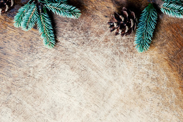 Christmas Background  with fir tree branches and pine cone  on rustic wooden board, space for text. Trendy Christmas wallpaper. Flat lay, Top view.
