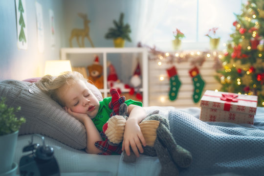 girl sleeping near Christmas tree