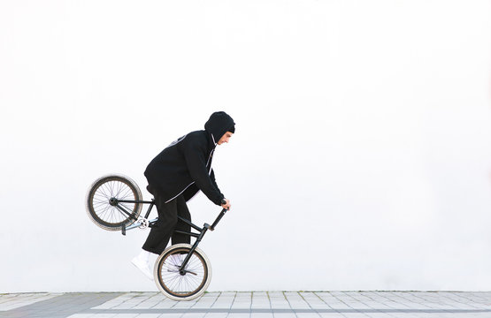 Bmx racer makes a trick in against the background of a white wall. Bmx rider with a bicycle in flight on a white background. Street bmx freestyle. Copyspace