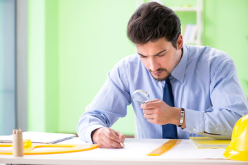 Young male architect working at the project