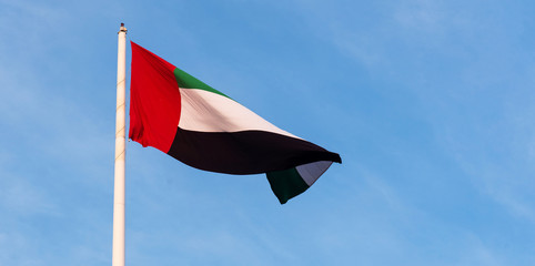 United Arab Emirates flag against blue sky