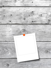 Blank square instant photo frame on grey wooden background