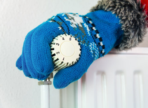 Hand with glove turning heating valve open in winter