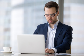 Tensioned or surprised caucasian man is sitting in office and typing on laptop. Serious and concentrated male in suit is working at notebook and looking resent and worried