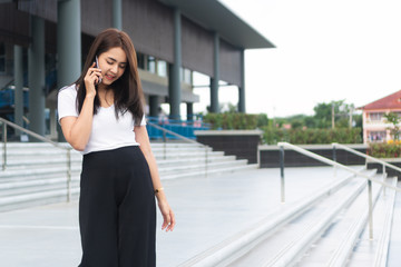 Young asian businesswoman in casual is talking on her mobile phone outdoor.