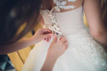 Bridesmaid tying a bow on a bride's elegant wedding dress.