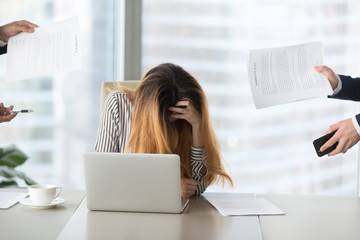 Young woman feeling desperate at work, tired of work. Suffers from exhaustion, deadline. Too much work, annoying colleagues, clients.