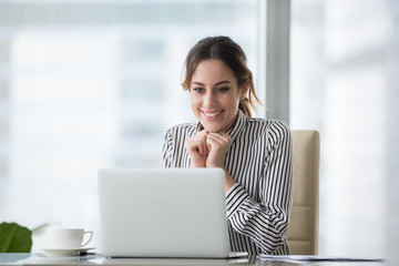 Happy smiling young woman looking at laptop screen. Excited businesswoman received good business offer, business email. Receiving good news concept, got promoted, achieved opportunity concept