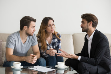 Young couple, family at meeting with realtor, interior designer, decorator, landlord, banker, financial advisor. Employee consulting, explaining Decision making doubting client customer
