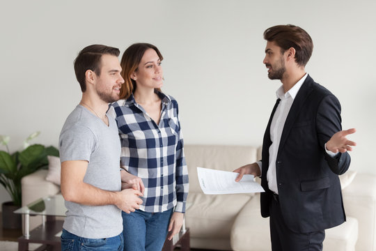Realtor, landlord consulting, explaining terms of contract to tenants. Young millennial couple, family at meeting with interior designer, banker, financial advisor. Happy customer, client making deal