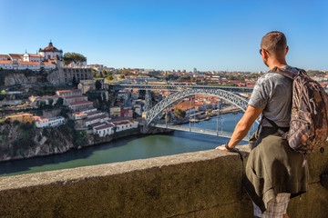 A young man admires the scenery of Porto, the Douro River. View of the bridge of San Luis.