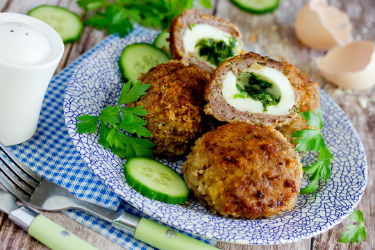 Meatballs stuffed with boiled eggs and green herbs butter in bread crumbs