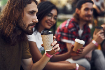 Calm bearded young man sitting next to his friends and thoughtfully looking into the distance while drinking coffee