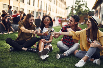 Cheers. Positive young friends wearing casual clothes and sitting on the grass with cups of coffee in their hands and smiling