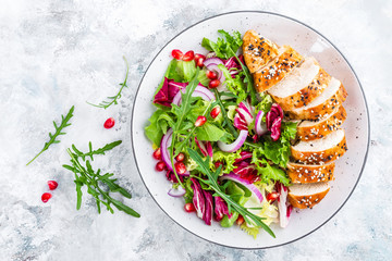 Poster Klaar gerecht Grilled chicken breast, fillet and fresh vegetable leafy salad with arugula and pomegranate on plate