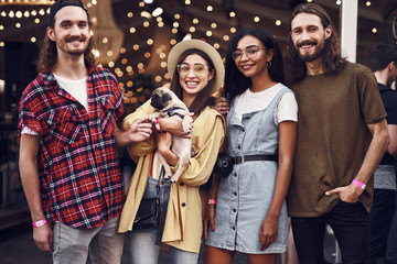 Cheerful relaxed young people wearing casual clothes and smiling while standing with adorable puppy