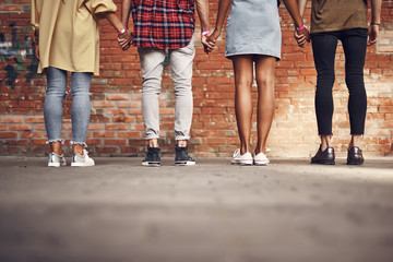 Holding hands. Confident close people in casual clothes standing in front of the brick wall and holding hands