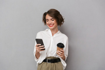Wall Mural - Photo of european woman 20s holding takeaway coffee and using cell phone, isolated over gray background